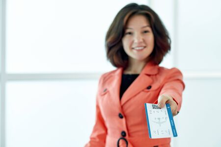 Business woman giving tickets waiting for departure in airport.