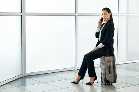 Young asian woman at the airport with trolley bag, talking on the phone and smiling. Stock Photo