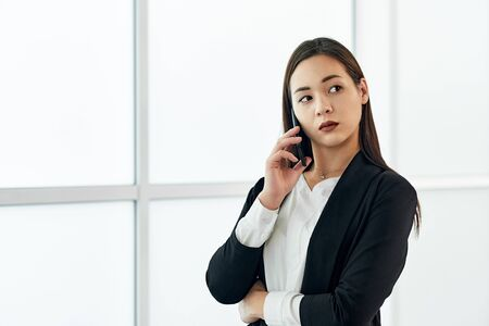 Asian Business woman talking on the phone. Portrait of beautiful girl in office on white background. Stock Photo