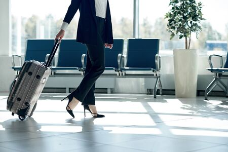 Legs of young businesswoman with baggage in airport
