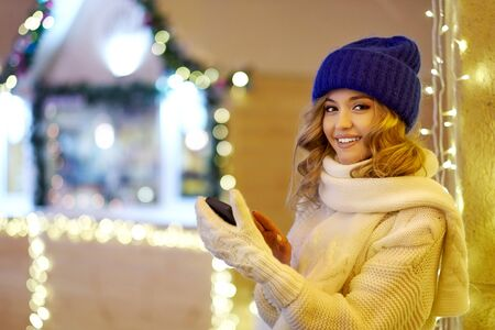 Woman calling congratulate with Christmas or New Year. Female with smartphone at Festive fair. Standard-Bild