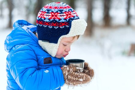Outdoor portrait Child blowing on hot tea from a flask in winter park