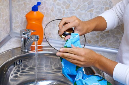 hands wipe pans cap with a towel. Wash dishes