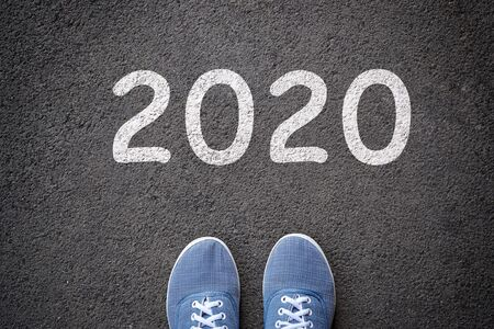 Dlue jeans casual shoes standing on the asphalt concrete road and white sign to new year 2020