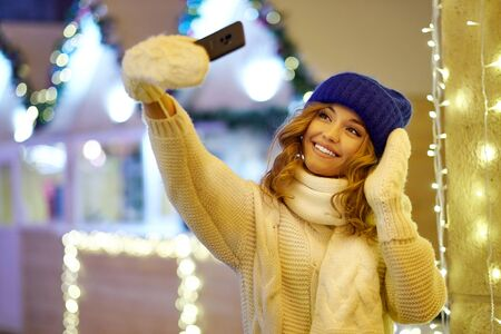 Woman taking selfie with garlands and holiday lights on festive Christmas or New Year fair. Lady wearing classic stylish winter knitted sweater and mittens.