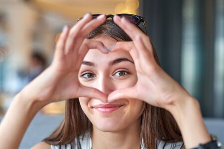 Beautiful woman looking through heart gesture made with hands.