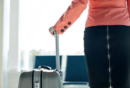 Young business woman at the airport with trolley bag, waiting for departure.