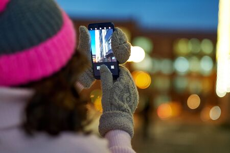Woman taking photo to smartphone with garlands and holiday lights on festive Christmas or New Year fair.