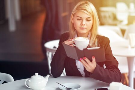 Young woman in cafe reading an ebook and drinking coffee