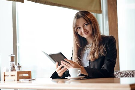 Young woman in a cafe reading an ebook and drinking coffee.