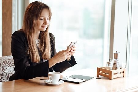 Young business woman using her smart phone and smiling in coffee shop. Stock fotó