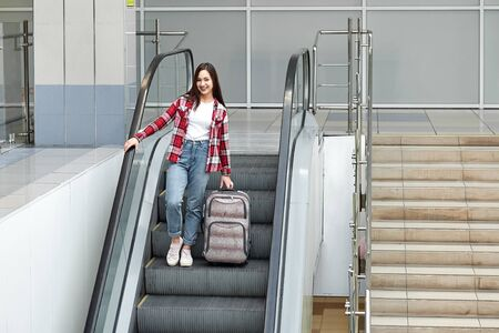 Asian girl with suitcase down the escalator in airport.