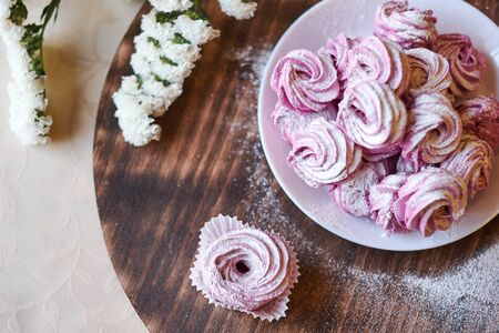 confectioner sprinkles icing sugar with dessert. Powder sugar falls on fresh perfect cupcakes or meringues