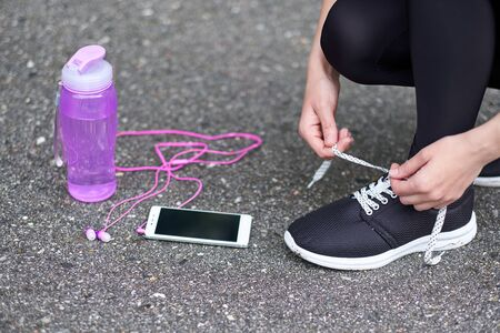 runner woman tying running shoes laces getting ready for race on run track stadium with bottle of water and phone with headphones Фото со стока