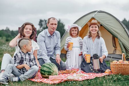 Happy family having picnic in meadow on a sunny day. Family Enjoying Camping Holiday In Countryside.