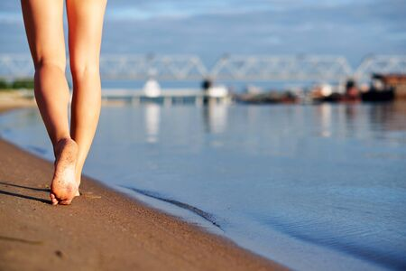 Woman legs and feet walking on the sand of the beach with the sea water in urban city background.