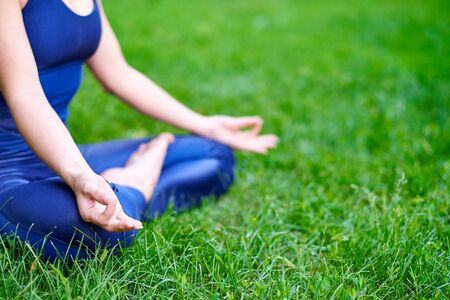 Yoga. Young woman practicing yoga meditation in nature at the park. lotus posture. Health lifestyle concept.