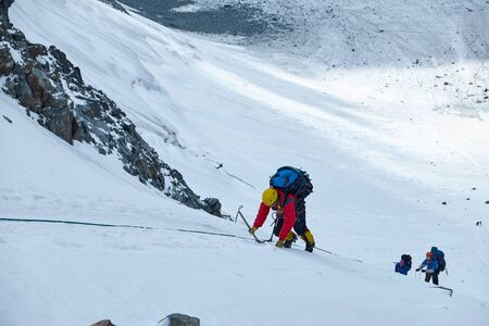 Bunch of mountaineers climbs to the top of a snow-capped mountain Stockfoto