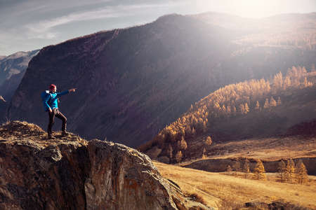 Hiker with backpack standing on top of a mountain with raised hands and enjoying sunrise 免版税图像