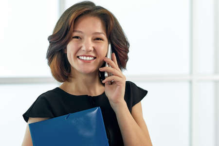 Business woman talking on the phone. Portrait of beautiful girl in office on white background.