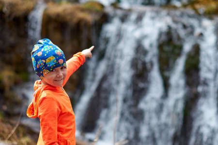 Happy child little girl points finger at waterfall. Outdoor sports portrait close-up