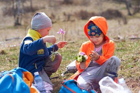 little boy gives girl bouquet of wild flowers. Hiking outdoor portrait Foto de archivo