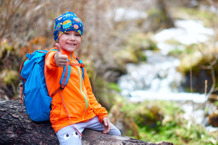 Hiking child little girl travel with backpacks thumb up. Outdoor sports portrait close-up