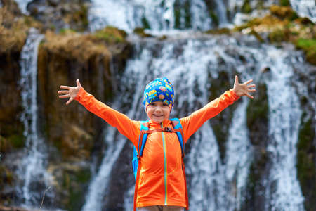 Happy child little girl travel with backpacks near a waterfall. Hands to the side. Outdoor sports portrait close-up