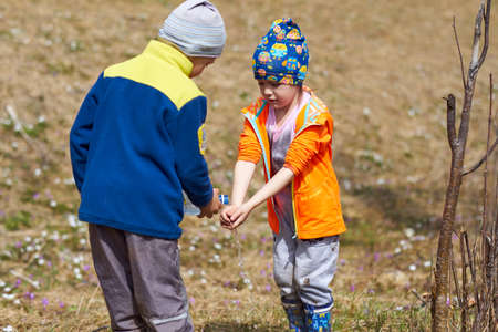 little boy helps a girl wash her hands. He pours water from a bottle. Hygiene in a hike in nature