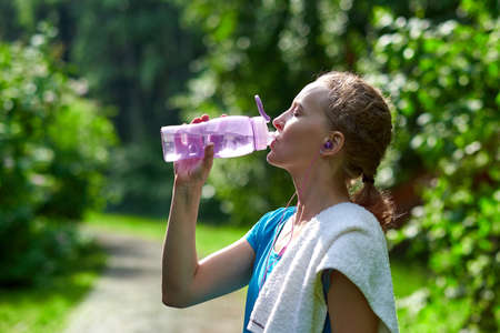 Fitness woman drinking water after running training in summer park.