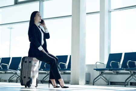 Young asian woman at the airport with trolley bag, talking on the phone and smiling. Foto de archivo