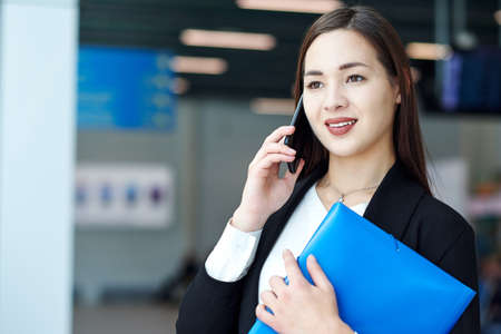Asian Business woman talking on the phone. Portrait of beautiful girl in office or meeting room.
