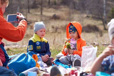 little boy gives girl bouquet of wild flowers. Mother takes pictures of children on phone