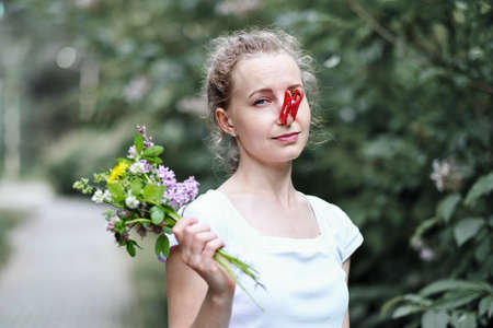 Funny Girl Trying Desperate Measures to Fight Spring Allergies to Flowers. Woman protecting her nose from allergens with clothes peg