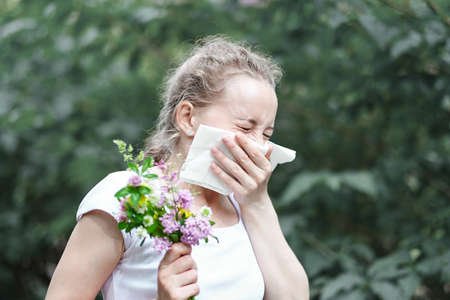 Pollen allergy, womansneezing with bouquet of flowers. Concept: seasonal allergy.