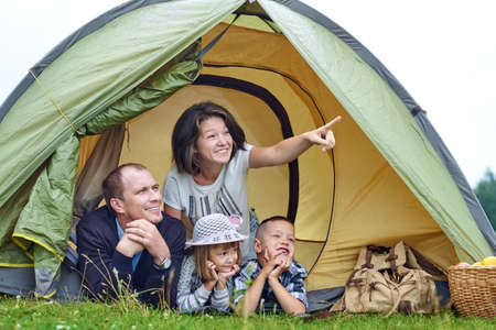 Family Parents and two children in camp tent. Happy Mother, father, son and daughter on Summer vacation. Mom showing something in distance