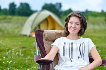 young woman freelancer sitting on chair and relaxing in front of tent at camping site in forest or meadow. Adventure traveling in national park. leisure, vacation, relaxation