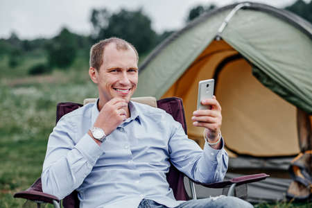 young man freelancer sitting on chair and using smart phone. Relaxing in front of tent at camping site in forest or meadow. Remote work and outdoor activity in summer.
