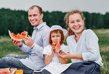 Happy family at a picnic eating watermelon. Mother, father and child at a picnic in meadow or park.
