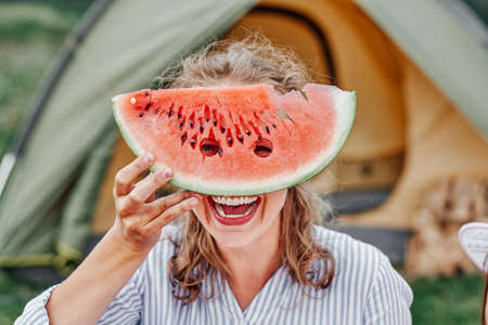 Funny woman eating watermelon on a picnic. Girl closed her eyes with a watermelon, looking into the holes.
