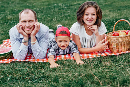Happy family resting in nature. Mother, father and child Enjoying and lying on checkered plaid in meadow.
