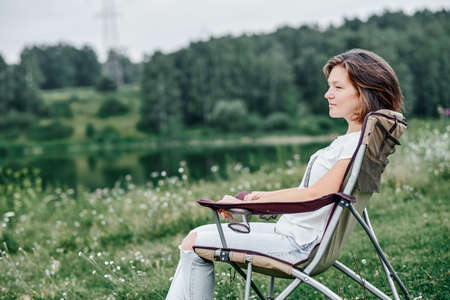 young woman freelancer sitting on chair and relaxing in nature near the lake. Outdoor activity in summer. Adventure traveling in national park. leisure, vacation, relaxation. Foto de archivo