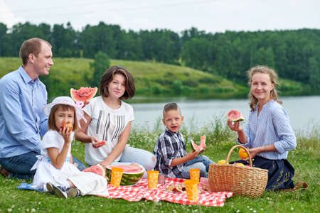 Happy family eating watermelon at a picnic. Picnic in the meadow or park near the lake. Young friends and their children in nature. Foto de archivo