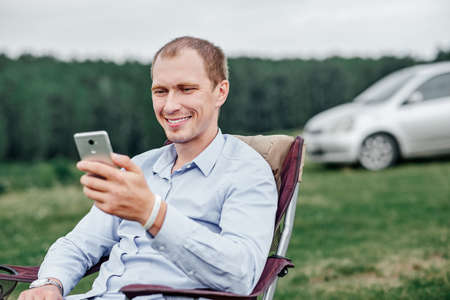 young man freelancer sitting on chair and using smart phone at camping site in forest or meadow. Remote work and outdoor activity in summer.