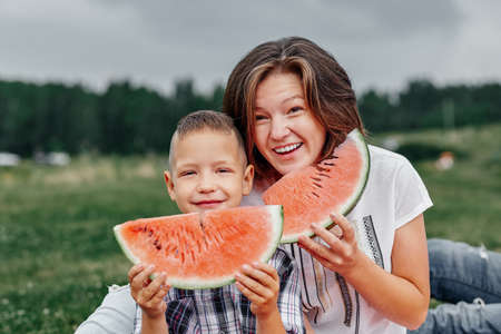 Mother and son eating watermelon in meadow or park. Happy family on picnic. outdoor portrait. Foto de archivo