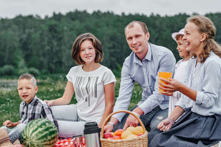 Happy family at a picnic. Picnic in the meadow or park. Young friends and their children in nature.