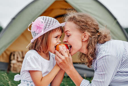 Mother and daughter eating apple near a tent in meadow or park. Happy family on picnic at camping.