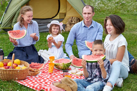 Happy family eating watermelon at picnic in meadow near the tent. Family Enjoying Camping Holiday In Countryside.
