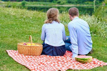 Young couple in love on picnic sitting on tablecloth in red cell. Love couple resting in nature in meadow or park.