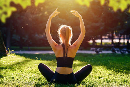 Yoga. Young woman practicing yoga meditation in nature at the park. Health lifestyle concept. Foto de archivo